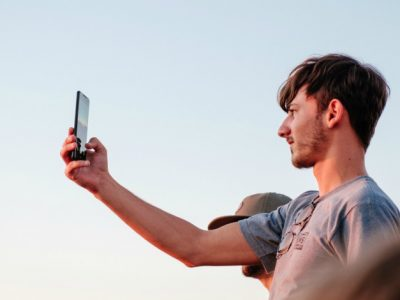 young man standing outside filming an Instagram Live