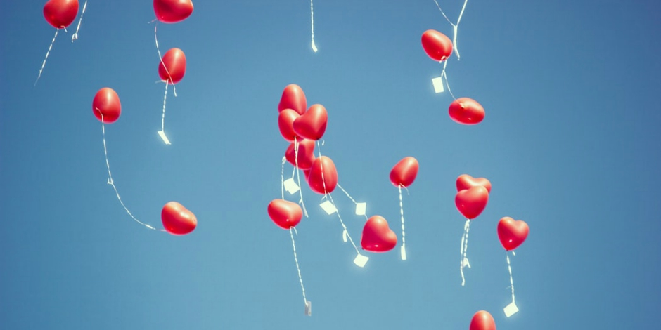 red heart balloons floating up into the sky