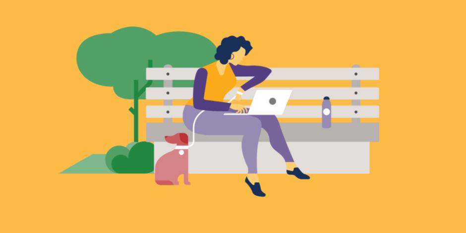 woman sitting on park bench with laptop and dog